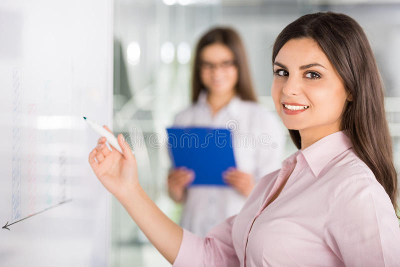 Business. Two beautiful office workers drawing business strategy on flip chart stock photo