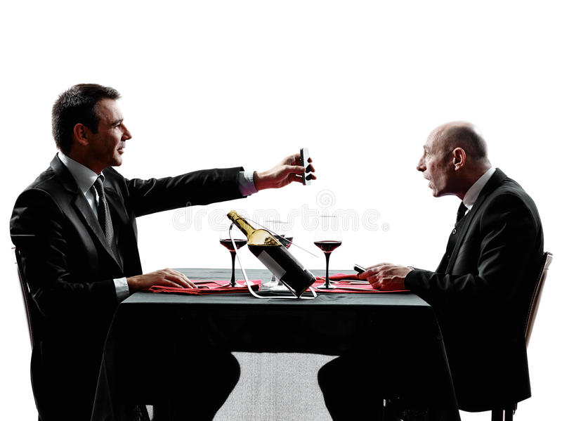 Business using smartphones dinner silhouettes. Two businessmen dinning using smartphones in silhouettes on white background stock image