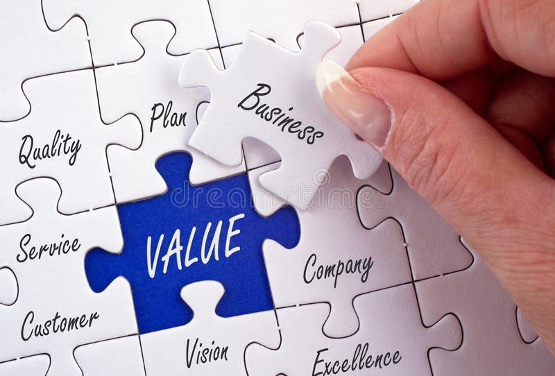 Business values. Text 'business' written in script (held in a female hand) on a jigsaw piece matching a missing piece marked 'value', surrounded by other pieces stock photo