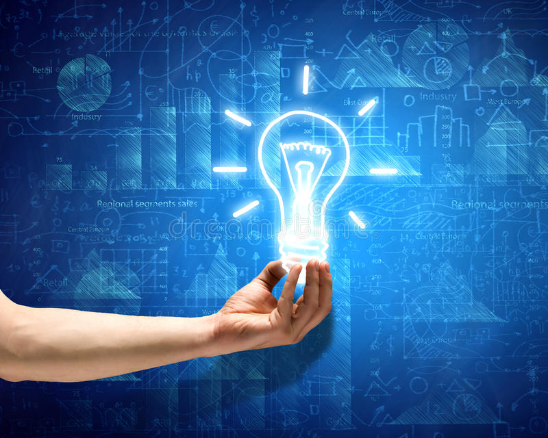 Business vision. Close up of hand holding light bulb with sketches at background royalty free stock photo