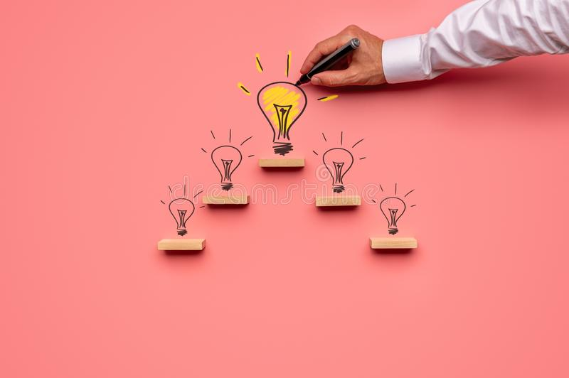 Business vision and idea concept. Businessman drawing light bulbs on pink background royalty free stock photography