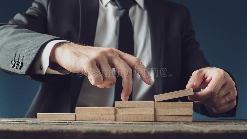 Business vision and progress. Businessman assembling stairway of wooden pegs as he walks his fingers upwards in a conceptual image royalty free stock photography
