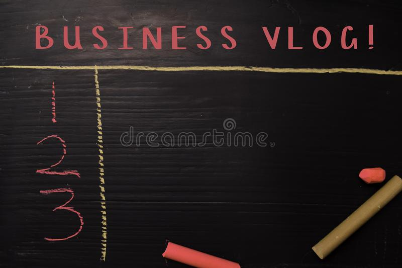 Business Vlog! written with color chalk. Supported by an additional services. Blackboard concept stock images