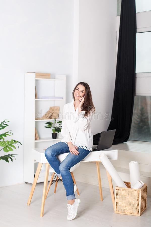 Business vumen. Young girl working in the office. The girl calls on the phone and sits on the table. Calling customers of the comp. Any.  Positive young manager stock photo