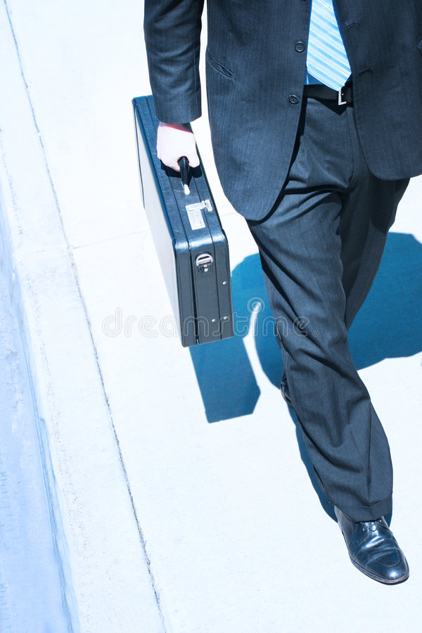 Business Walk. Businessman walks with briefcase down the street stock photo
