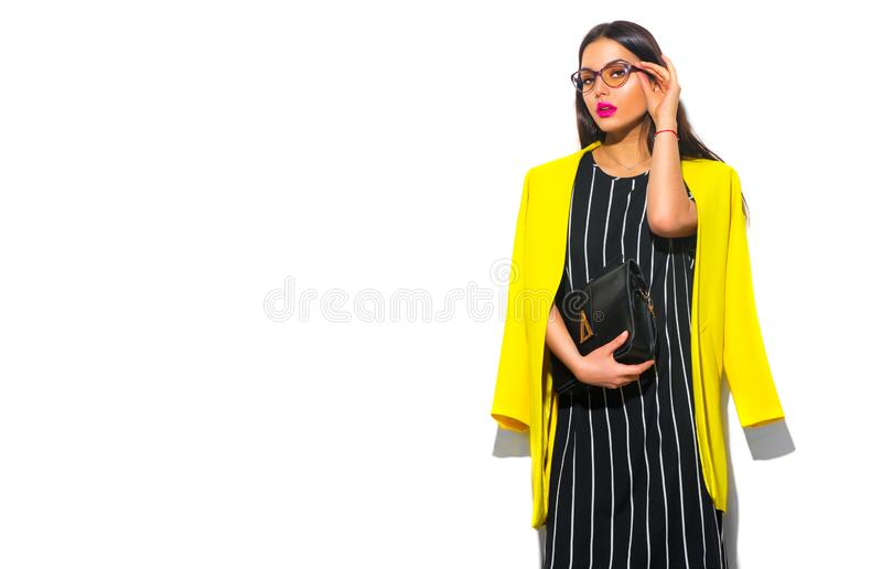 Business wear look style. Beauty fashion model girl in trendy yellow blazer wearing glasses, on white background. Beautiful young brunette woman posing stock photo