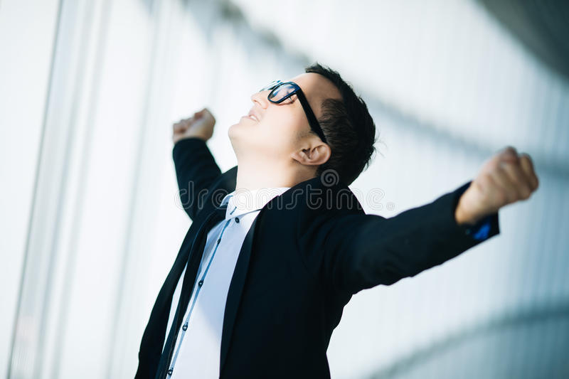 Business winner. happy young man in formalwear celebrating, gesturing, keeping arms raised. And expressing positivity in panoramic window office royalty free stock photography