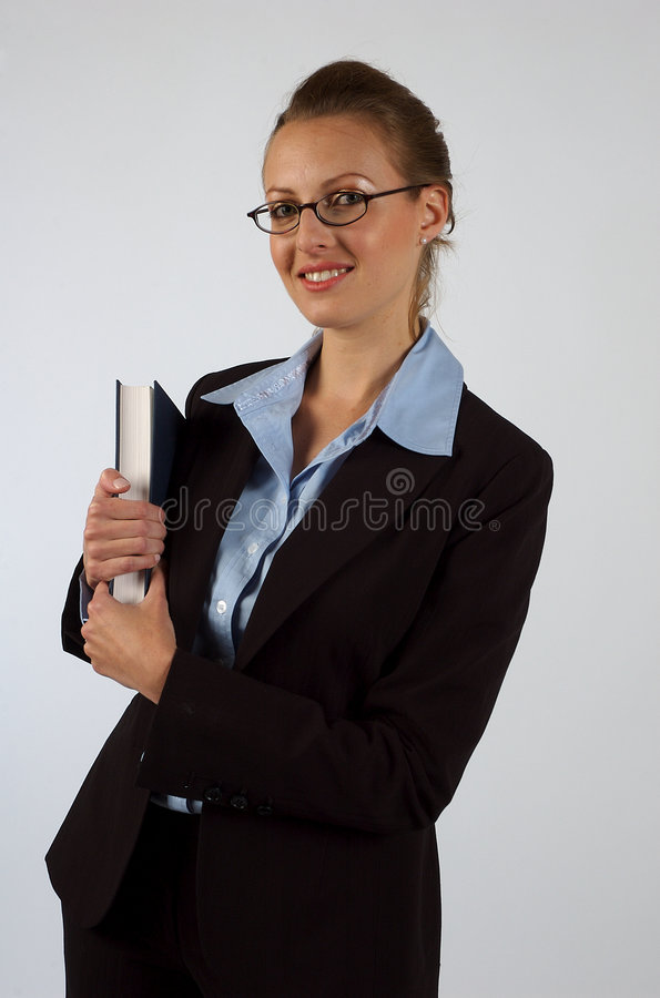 Business Woman. A woman in a business suit, looking into an open book, with the frame of her glasses in her mouth stock image