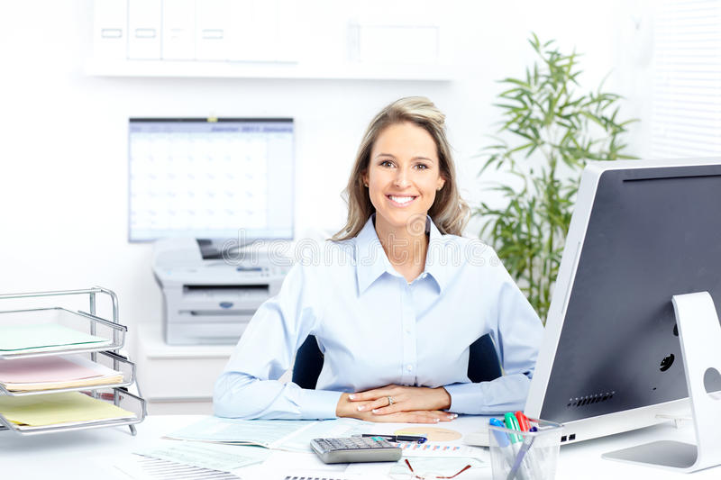 Business woman. Young smiling business woman working with computer stock image