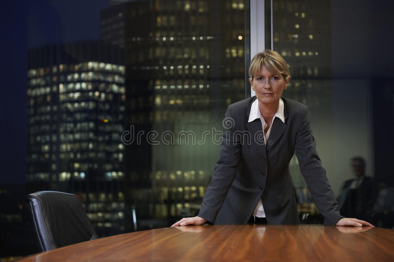 Business woman. Senior Business woman leaning on table in boardroom looking at camera stock image