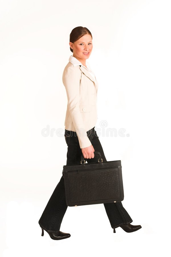 Business Woman #223(GS). Business woman dressed in jeans and a beige jacket. Walking. Movement royalty free stock images