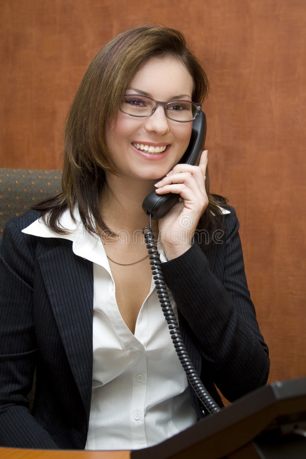Business woman. Attractive brunette business woman wearing business suit on the phone royalty free stock photo