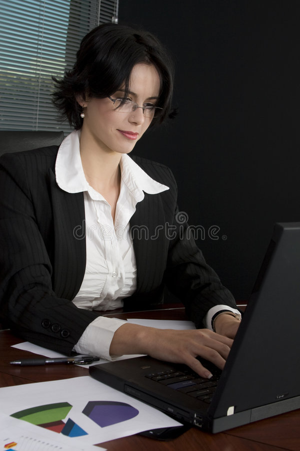 Business woman. Attractive brunette business woman working at her desk royalty free stock photos