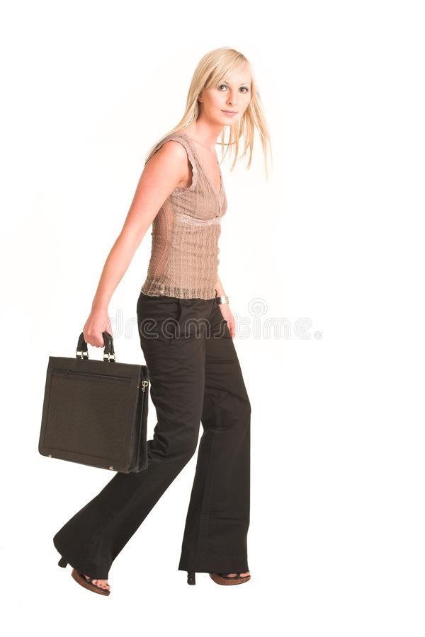 Business Woman #308. Blond business woman dressed in black trousers and a beige shirt. Walking, carrying a black leather suitcase. Movement on right foot royalty free stock photo