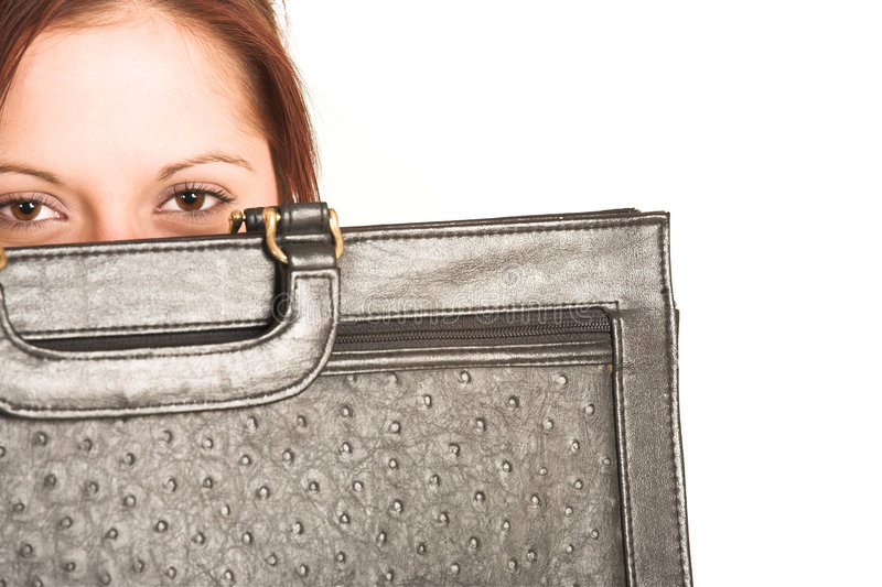 Business Woman #335. Business woman with brown hair, peeking over a leather suitcase. Copy space royalty free stock images