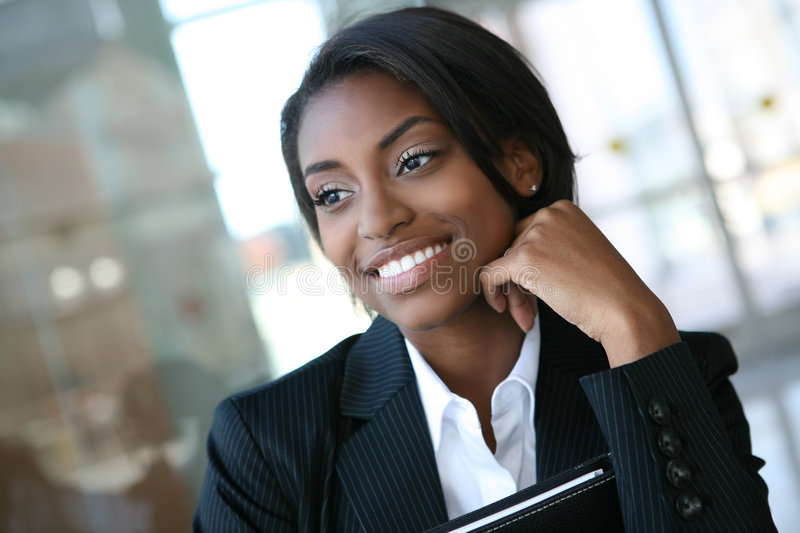 Business Woman. A pretty african american business woman at her company stock image
