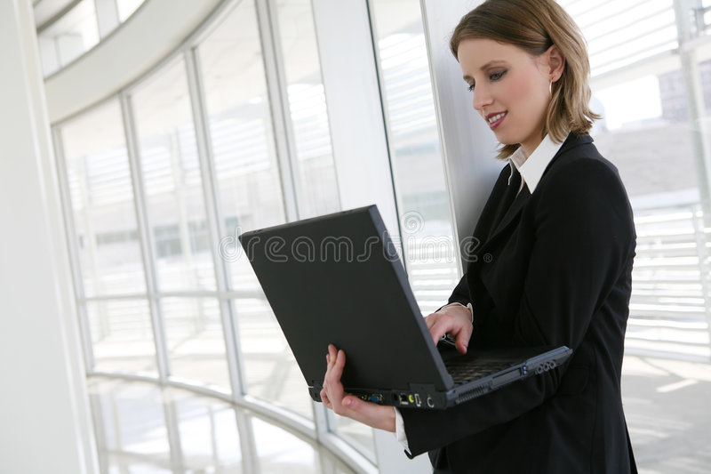 Business Woman. A beautiful blonde business woman in company holding laptop royalty free stock photo