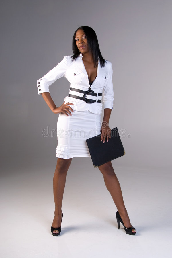 Business woman. Attractive African American business woman wearing a white suit, standing up, with one hand on her hip and holding a folder with the other hand royalty free stock photography