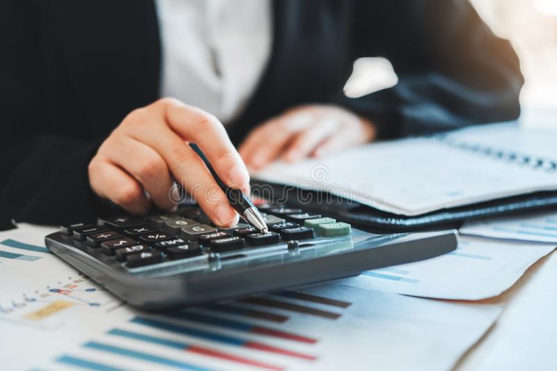 Business woman  Accounting Financial investment on calculator Cost Economic business and market stock photography