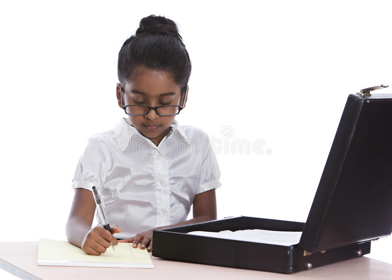 Business Woman. Adorable little girl dressed as a business woman working at a desk with her brief case open. Isolated on white stock photo
