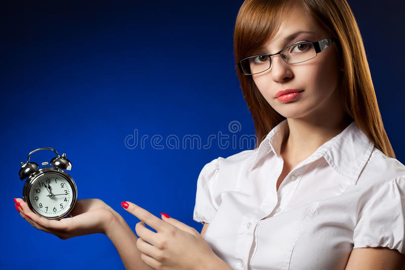 Business woman and alarm clock. Deadline concept over blue stock photography