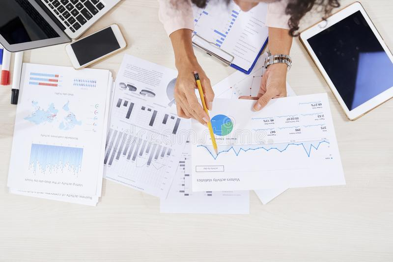 Business woman analyzing various charts stock photography