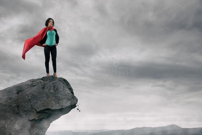 Business woman as a super hero on the peak of a mountain royalty free stock images