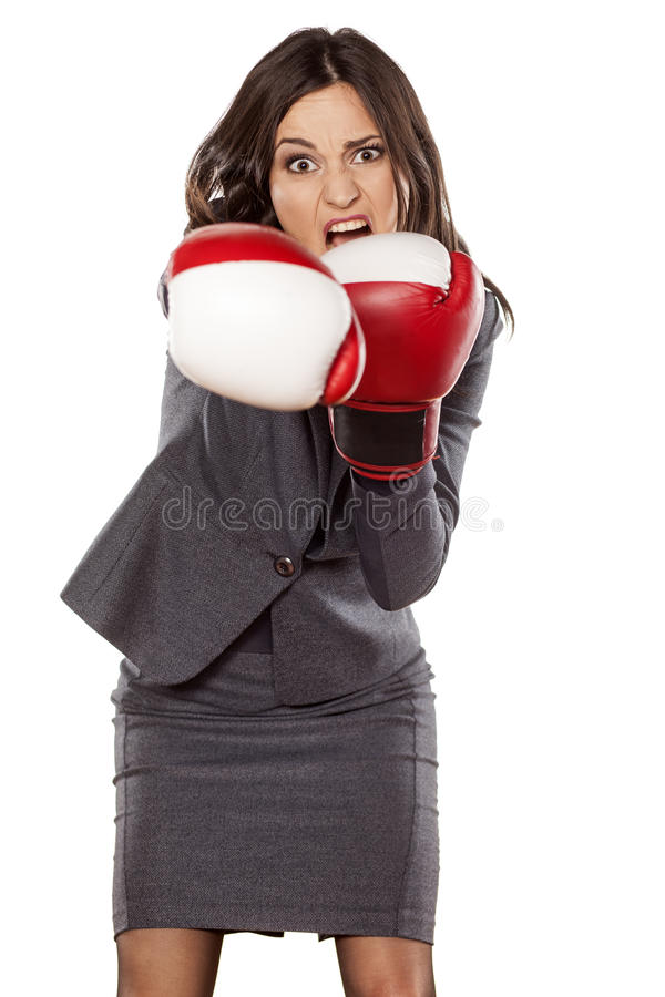 Business woman attack. Front view of an angry business woman, attacking with boxing gloves royalty free stock images