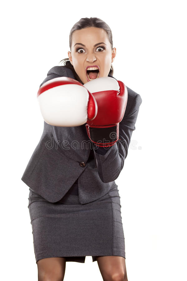 Business woman attack. Front view of an angry business woman, attacking with boxing gloves stock images