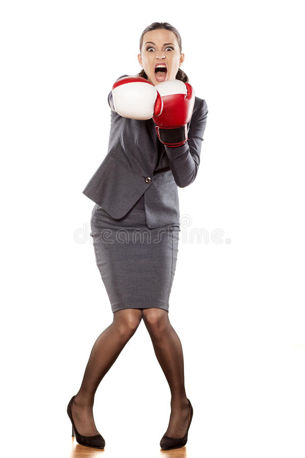 Business woman attack. Front view of an angry business woman, attacking with boxing gloves royalty free stock photography