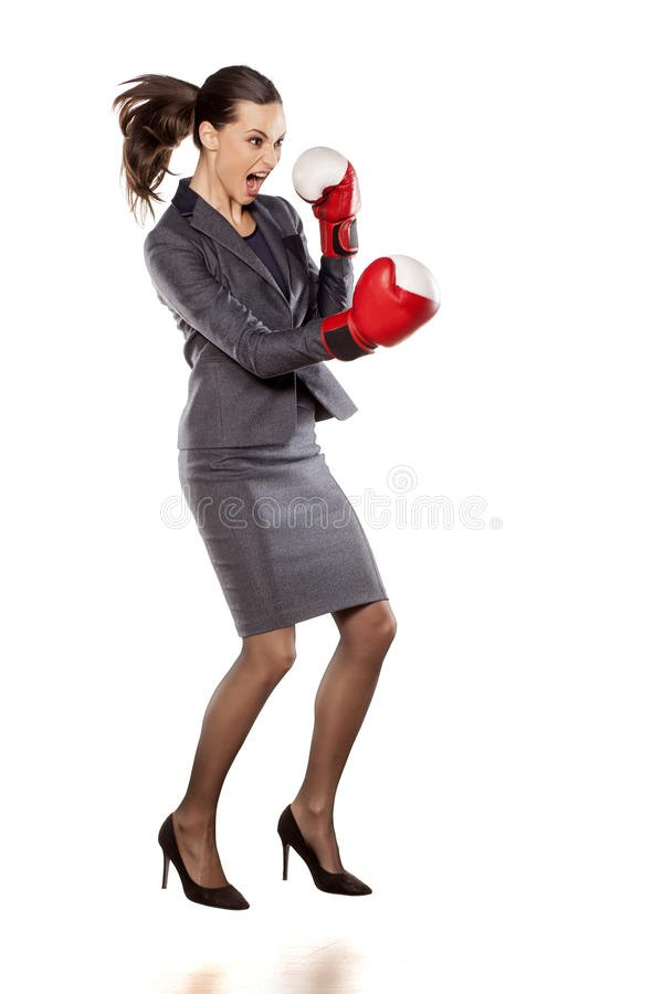 Business woman attack. Profile of an angry business woman, attacking with boxing gloves royalty free stock photography
