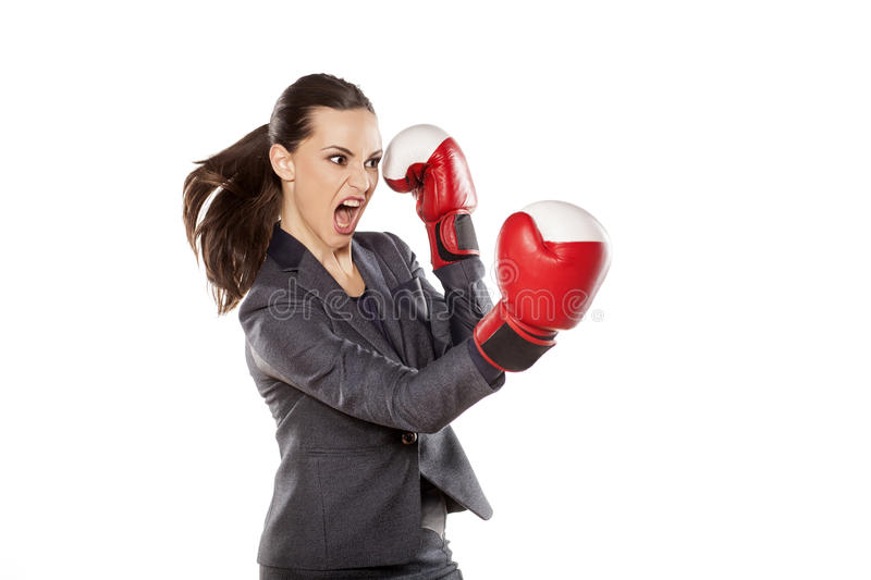 Business woman attack. Profile of an angry business woman, attacking with boxing gloves royalty free stock photos