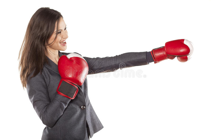 Business woman attack. Profile of a business woman, attacking with boxing gloves stock photography