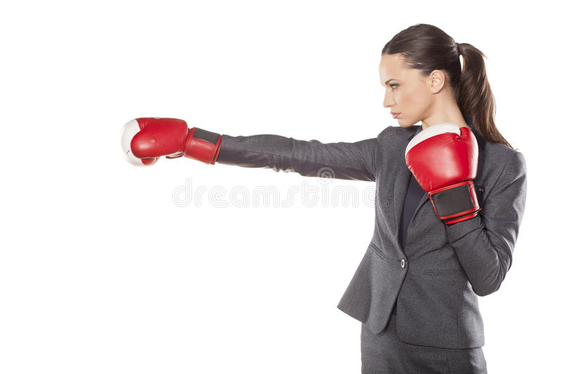 Business woman attack. Profile of a business woman, attacking with boxing gloves royalty free stock image