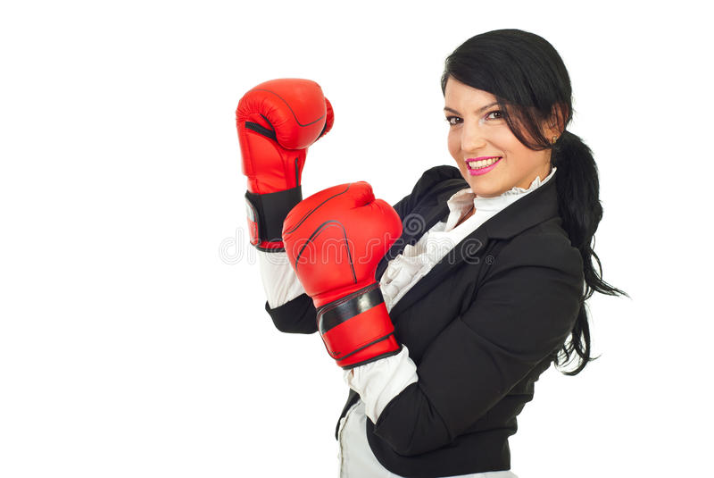 Business woman with attitude. Happy business woman with attitude standing in semi profile and wearing boxing gloves isolated on white background stock photo
