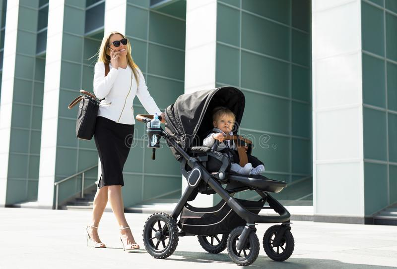 Business woman with baby carriage walking. Business women with baby carriage walking and talking on the phone stock photography