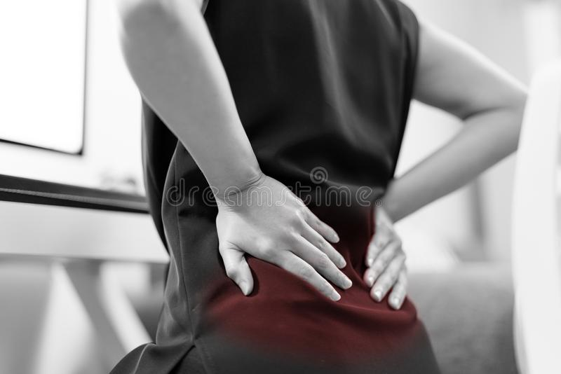 Business woman with back pain an office. Healthcare and medical concept - Black and White color image royalty free stock images