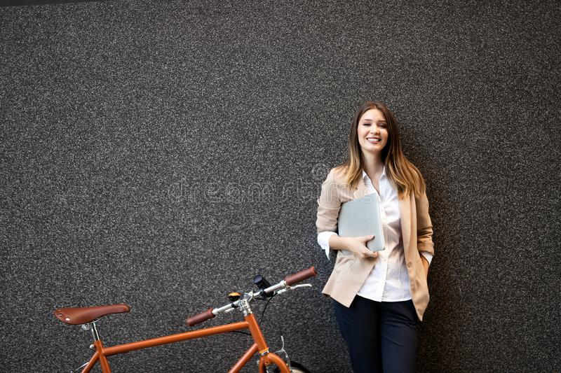 Business woman with bicycle to work on urban street in city. Transport and healthy lifestyle concept. Happy business woman with bicycle to work on urban street stock photo