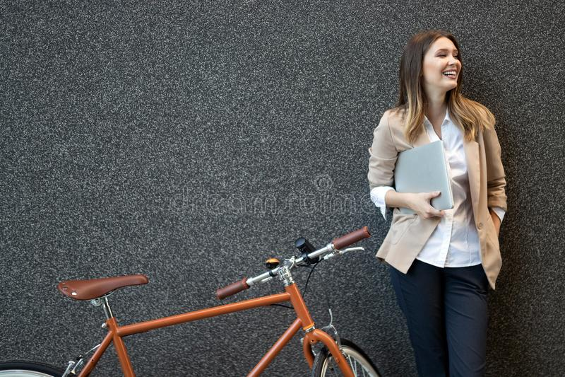 Business woman with bicycle to work on urban street in city. Transport and healthy lifestyle concept. Happy business woman with bicycle to work on urban street royalty free stock images