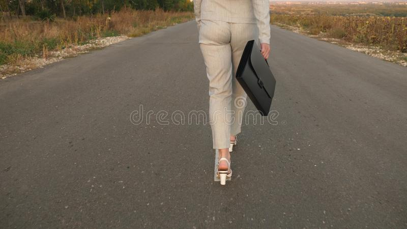 Business woman with black briefcase is walking in light suit and white high-heeled shoes are walking along asphalt with royalty free stock image
