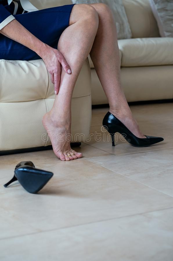 Senior lady suffering from leg pain. Business woman in black high heels massaging her tired legs with her hand. Varicose veins co royalty free stock photo
