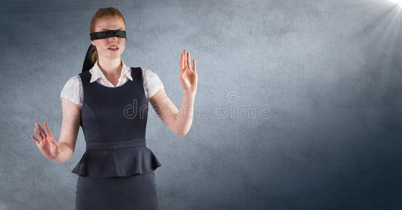 Business woman blindfolded against navy background with flare and grunge overlay royalty free stock images