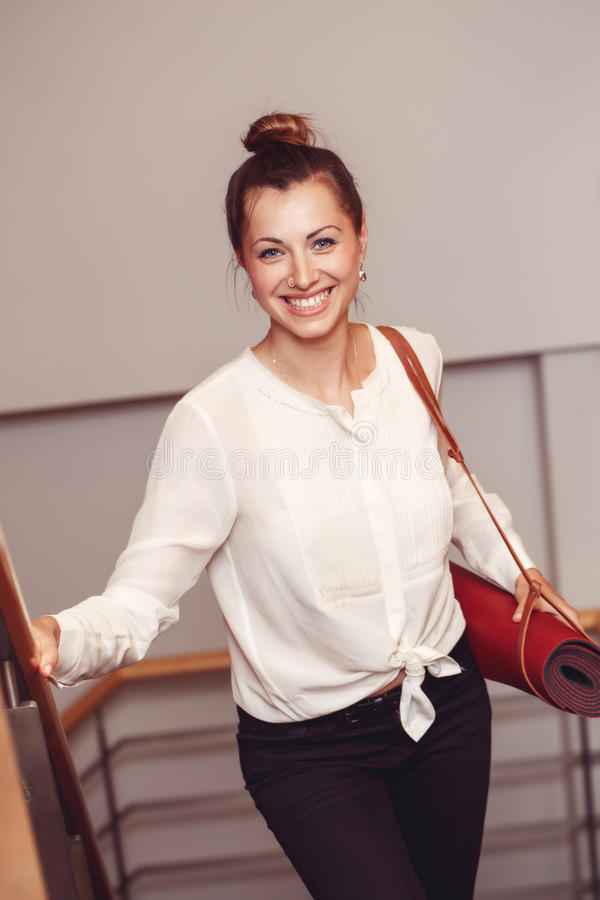 Business woman with blue eyes in white blouse shirt and black pants holding, carrying yoga mat in office royalty free stock photography