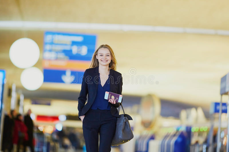 Business woman with boarding pass and passport in international airport royalty free stock photography