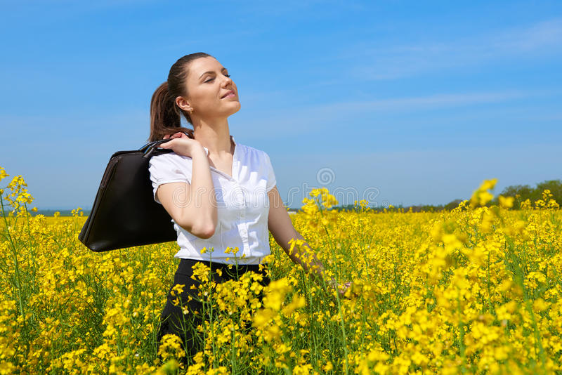 Business woman with briefcase relaxing in flower field outdoor under sun. Young girl in yellow rapeseed field. Beautiful spring la. Ndscape, bright sunny day royalty free stock photos