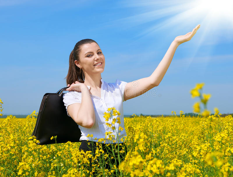 Business woman with briefcase relaxing in flower field outdoor under sun. Young girl in yellow rapeseed field. Beautiful spring la. Ndscape, bright sunny day royalty free stock image