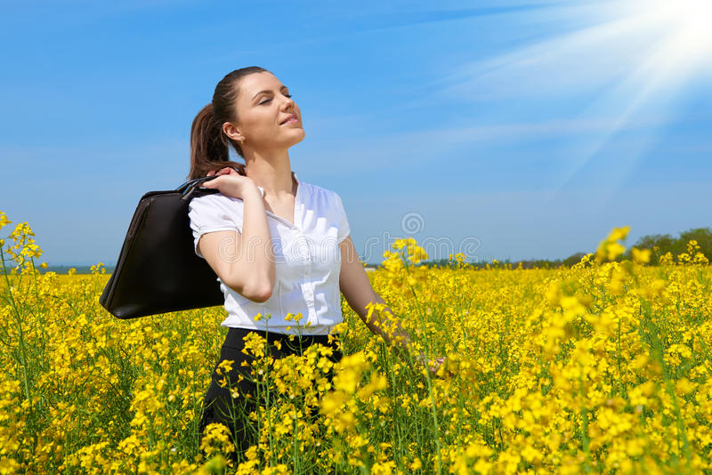 Business woman with briefcase relaxing in flower field outdoor under sun. Young girl in yellow rapeseed field. Beautiful spring la. Ndscape, bright sunny day stock photo