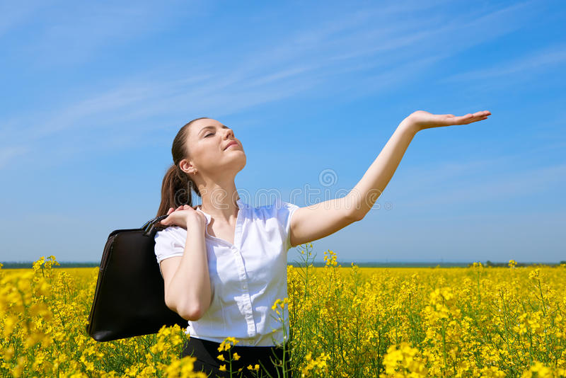 Business woman with briefcase relaxing in flower field outdoor under sun. Young girl in yellow rapeseed field. Beautiful spring la. Ndscape, bright sunny day stock photos