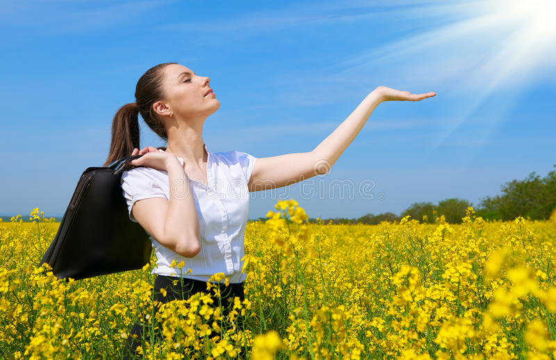Business woman with briefcase show palm to sun. Young girl in yellow flower field. Beautiful spring landscape, bright sunny day, r. Apeseed royalty free stock photo
