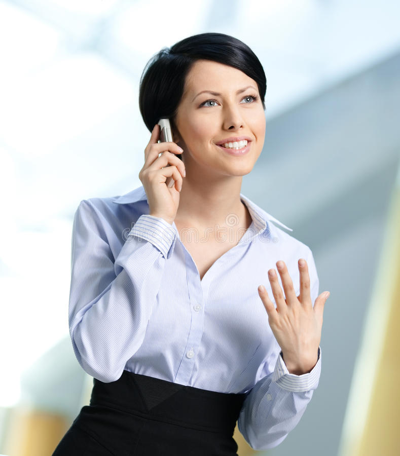 Business woman in business suit talks on telephone royalty free stock photography